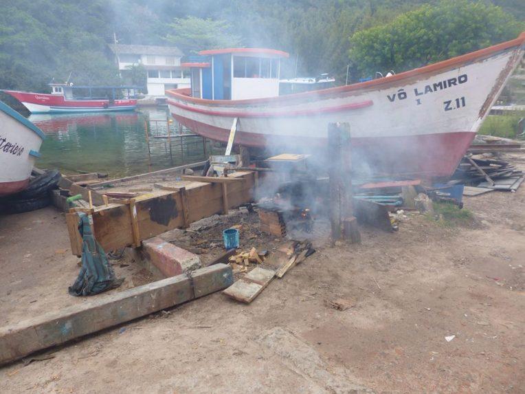 Tässä rakennetaan kalastusalusta. Lankut kuumennetaan uunissa höyryn ja nuotion avulla, jonka jälkeen niitä on helpompi taivutella aluksen muotoihin sopiviksi.